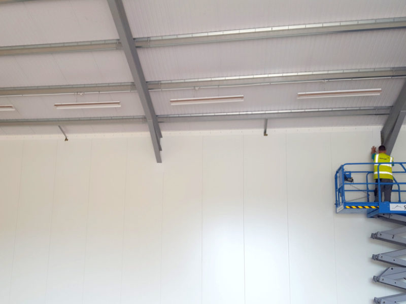 Installer fitting hygienic panels for retail store